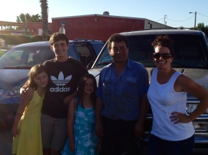 A grateful family poses with a generous man in front of the car he loaned us and the one he repaired.