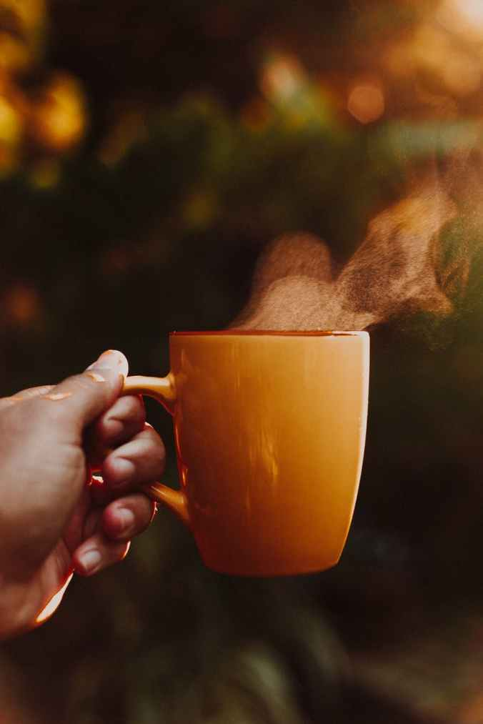 photo of a hand holding out a steaming cup